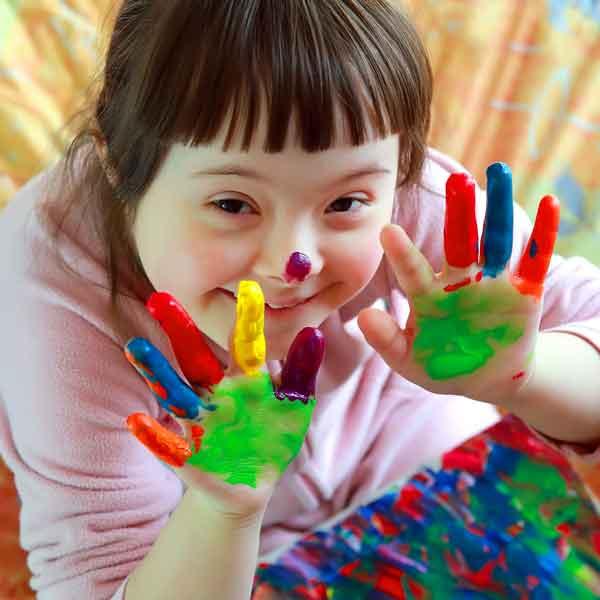 Fröhliches Mädchen mit bunten Fingerfarben an den Händen.